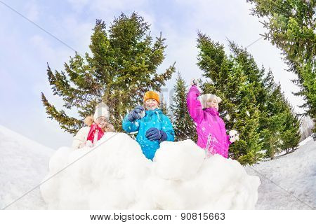 Girls and boy playing snowballs game in forest