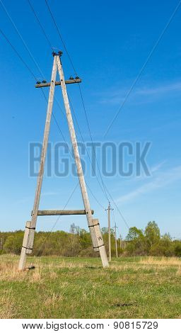 Wooden electric pillar against blue sky