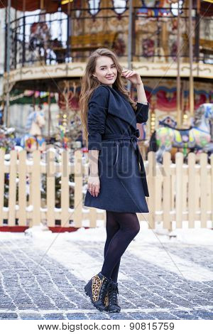 Young beautiful woman in stylish gray coat on a background of a winter street