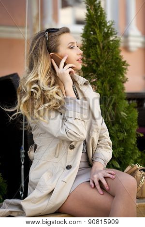 Young beautiful blonde woman calling by phone in a beige coat sitting on a bench in the street