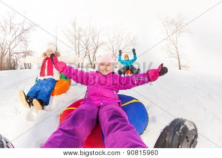 Girl and kids sliding down the hill on tubes