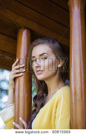 Beautiful young woman in yellow coat in autumn street