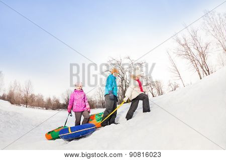 Children walking up the snowy hill and carry tubes
