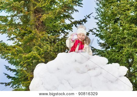 Beautiful small girl holds snowball in the forest