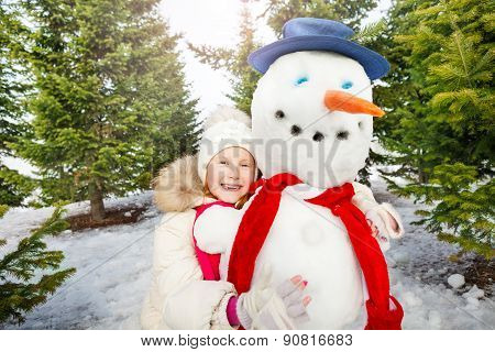 Close-up view of laughing girl and snowman