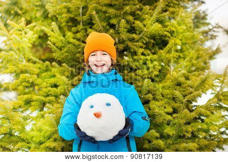 Laughing boy holding snowman's head in forest