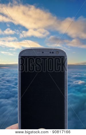 Smatrphone and cloudy sky. Idea for religious app, weather app, aerial transports, digital detox, taking shots, accessing apps, Internet, blogs and others. The blur image is a sky from Brazil