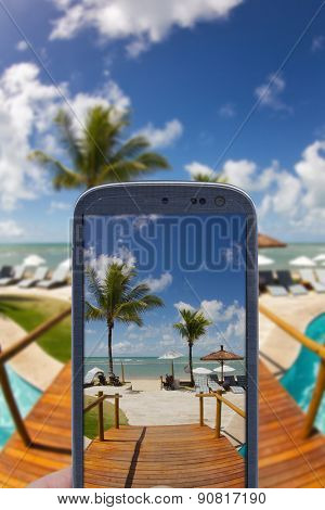 Smatrphone and a landscape. Idea of taking shots, accessing apps, Internet, blogs and others. The blur image is a sunny day at Arraial d'Ajuda Eco Resort in Bahia - Brazil.