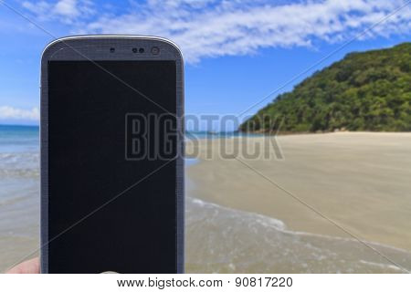 Smatrphone and a landscape. Idea of taking shots, accessing apps, Internet, blogs and others. The blur image is beach at As ilhas in Barra do Sahy, Sao Sebastiao, Sao Paulo - Brazil