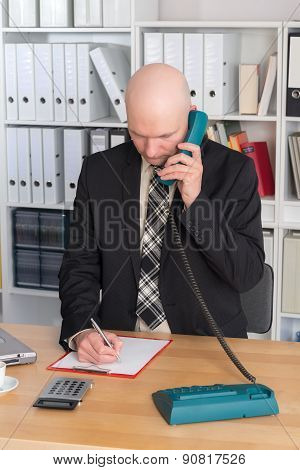 Young Businessman With Bald Head Is Calling