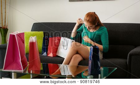 Latina Girl After Shopping Tries Fashion Necklace On Sofa