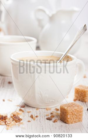 Cup of coffee with sugar cubs and milk jug