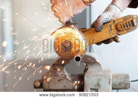 Man Cuts A Metal Pipe.