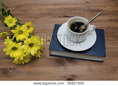 Cup Of Coffee And Book With Yellow Flowers Onwooden Table