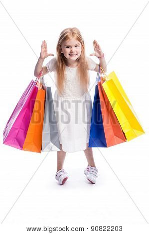 Fun Little Girl With Big Colourful Shopping Bags.