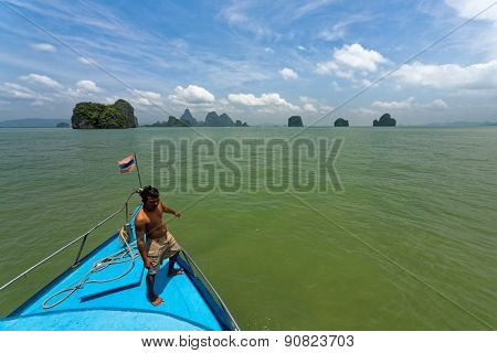 MARCH 12, 2008 - PHUKET, THAILAND: The navigator guides the boat captain on the approach to the islands near Phuket. This is a popular tourist destination for snorkelling and swimming.