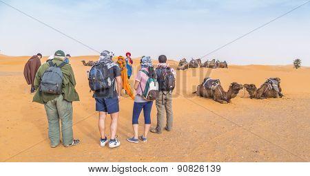 MERZOUGA, MOROCCO, APRIL 13, 2015: Tourists wait for a camel excursion into Dunes Erg Chebbi near Merzouga