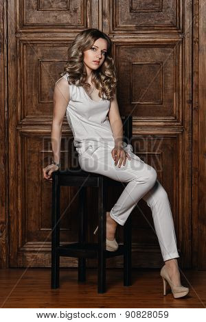 beautiful girl with curly hair in a white suit