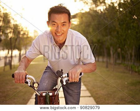 Asian Man Enjoying Outdoor Bike Riding In A Park At Sunset