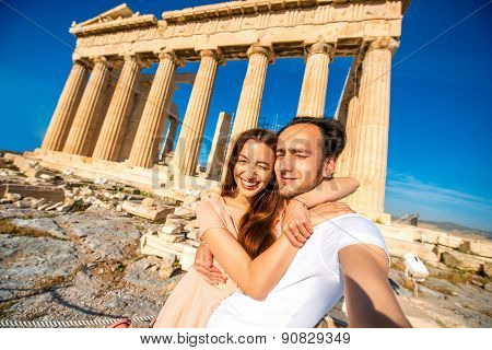 Young couple taking selfie picture with Parthenon temple on background in Acropolis