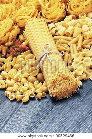 Mix of pasta on wood background