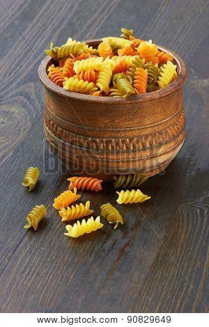 Fusilli italian pasta in wood bowl, on wood background