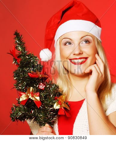 woman with Santa hat holding christmass tree