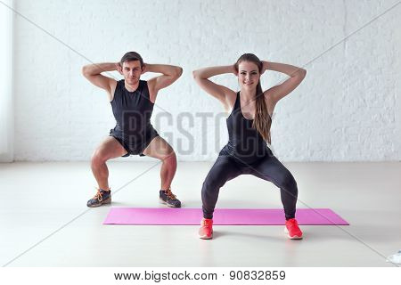 Fitness man and woman exercising squat exercise hands behind head concept sport, training, warming u