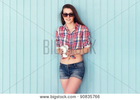 Outdoor summer closeup portrait of young stylish woman in shirt and denim shorts sunglasses holding