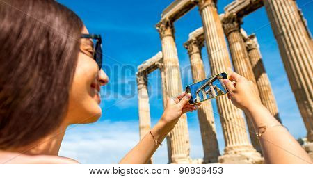 Woman photographing Zeus temple in Greece