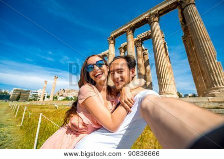 Young couple taking selfie picture with Zeus temple on background in Acropolis