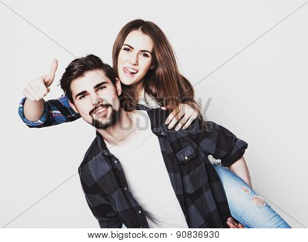 emotional, life style, happiness and people concept: Happy loving couple. Young man piggybacking his girlfriend. Studio shot over white background.Special Fashionable toning photos.