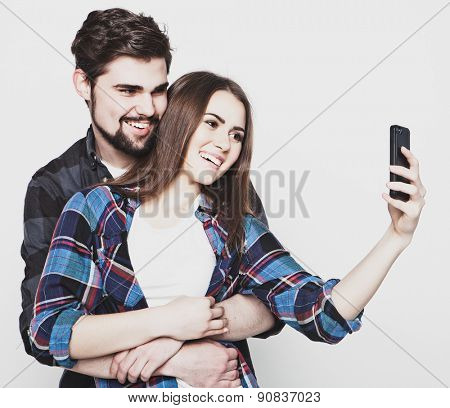 tehnology, internet, emotional  and people concept: Capturing happy moments together. Happy young loving couple making selfie and smiling.Special Fashionable toning.