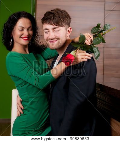 The modest young man with a rose and its girlfriend. Appointment in cafe
