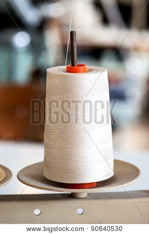 White Thread Roll On A Stand For Sewing