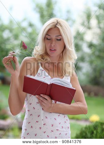 A young woman searches for the name of a flower in the directory