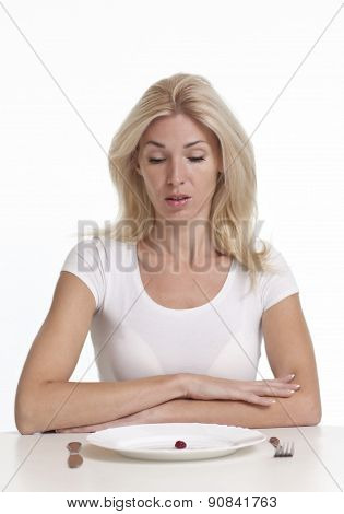 Woman sitting in front of an empty dish. Diet concept.