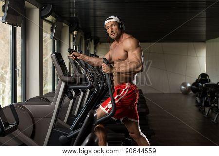 Mature Man Doing Aerobics Elliptical Walker In Gym