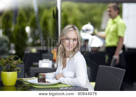 Very beautiful young woman, sit in Cafe and drink coffee