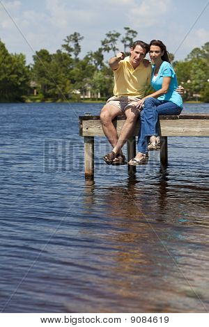 Happy Man And Woman Couple Sitting On A Pier By Lake