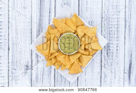 Some Nachos (with Guacamole) On Wood