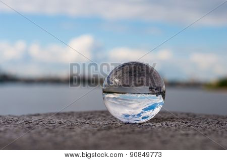 Glass transparent ball on river background and grainy surface. Water