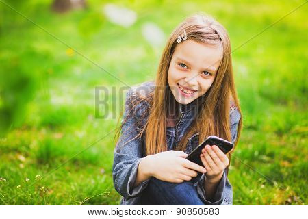 Portrait Of Smiling Teenage Girl With Mobile Phone