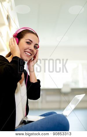 Young Woman Sitting Outdoors Listening To Music