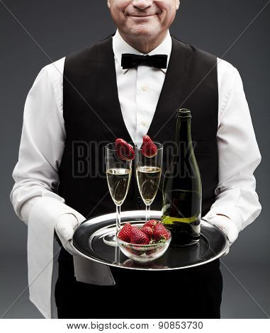 butler holding tray with two champagne flutes and bottle