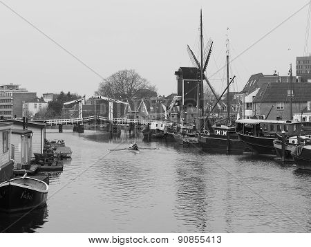 Canal with motor boats, a rowing boat and windmill