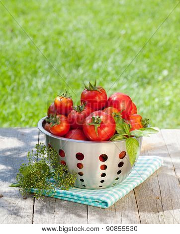 Fresh ripe tomatoes in colander on wooden table