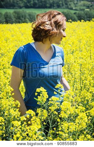 Young Woman Is Walking In Yellow Rapeseed Field