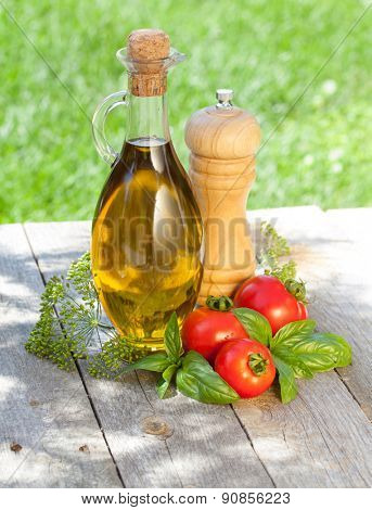 Olive oil bottle, pepper shaker, basil and ripe tomatoes on wooden table