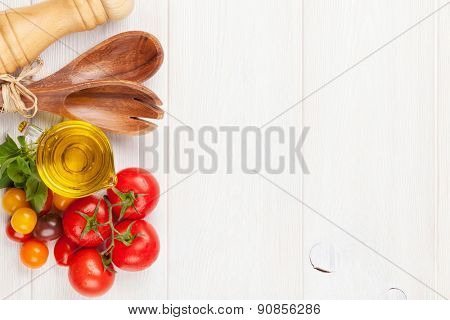 Fresh colorful tomatoes, basil and olive oil on white wooden table. Top view with copy space